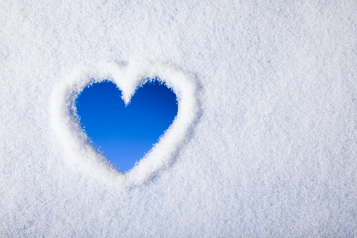 Photography of a Heart shape painted on a frozen window.