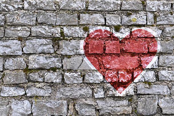 heart shape painted on stone brickwall - sprüche für die liebe stock-fotos und bilder