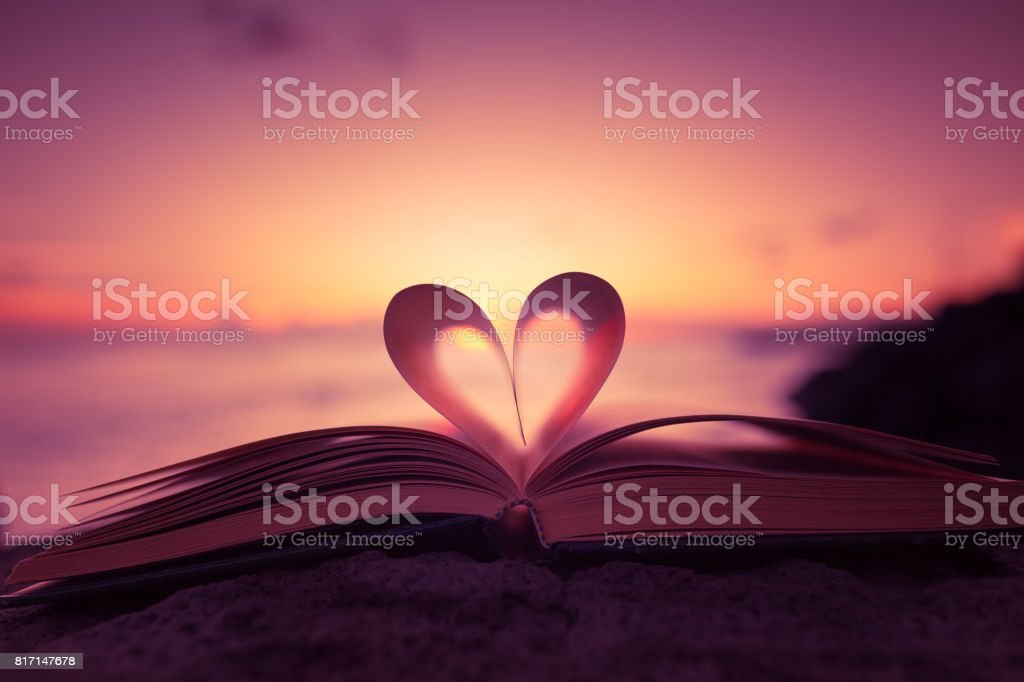 Heart shape paper book on the beach Heart from a book page against a beautiful sunset. Accessibility Stock Photo