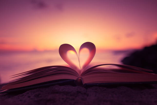 Heart shape paper book on the beach Heart from a book page against a beautiful sunset. amor stock pictures, royalty-free photos & images