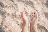 Hands of woman kids holding sandy to heart shape on beach. summer season.