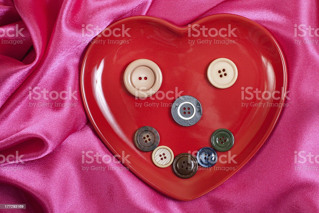 Heart shape plate with buttons on rosy wave background royalty-free stock photo