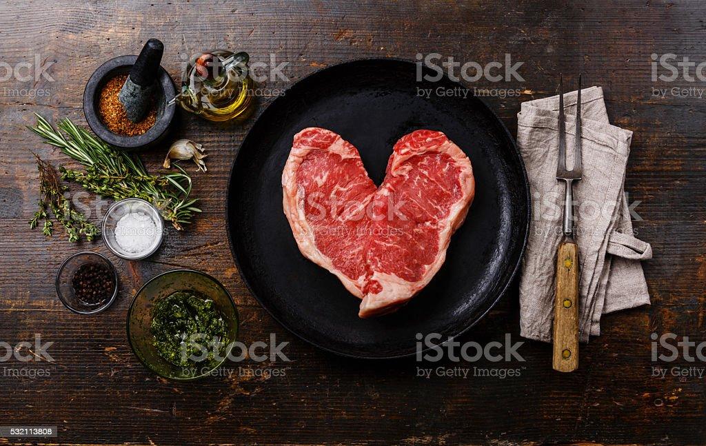 Heart shape Raw meat Steak on frying pan stock photo