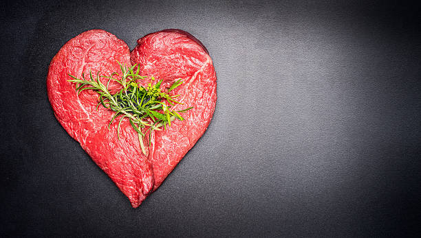 Heart shape raw meat with herbs on dark chalkboard background stock photo