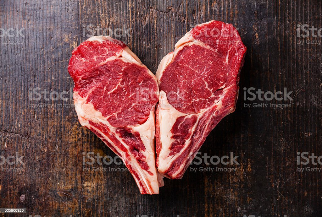 Heart shape Raw steak on bone stock photo