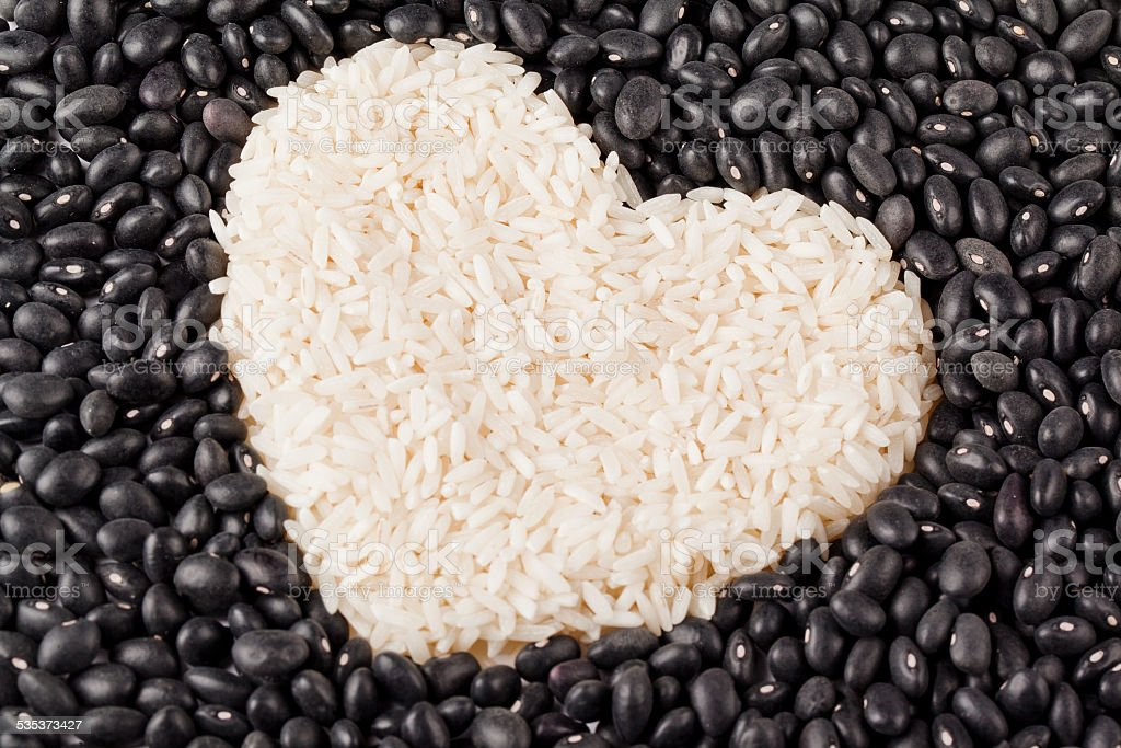 heart shape rice grains isolated on the dark beans stock photo