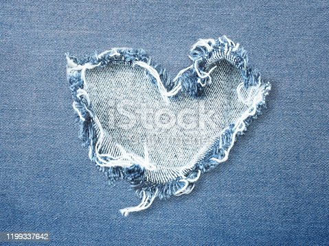 Heart shape ripped jean denim texture for Valentine's card background. Love concept.