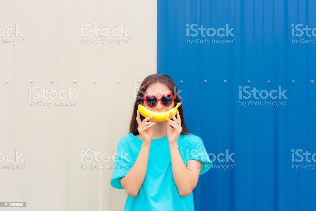 Heart Shape Sunglasses Woman with Funny Big Banana Smile stock photo