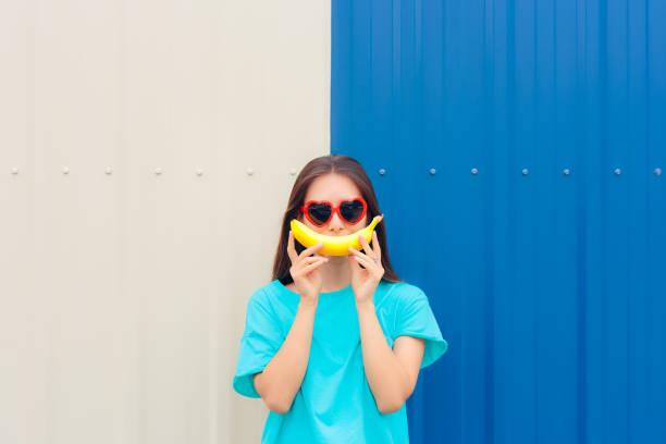 hart vorm zonnebril vrouw met grappige grote banaan glimlach - kalium stockfoto's en -beelden