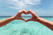 hand heart shape with Turquoise maldives water as background