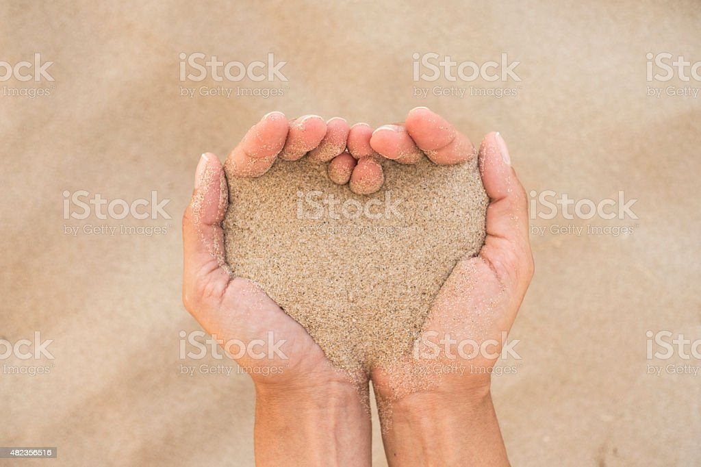 heart shape with handful of sea sand stock photo