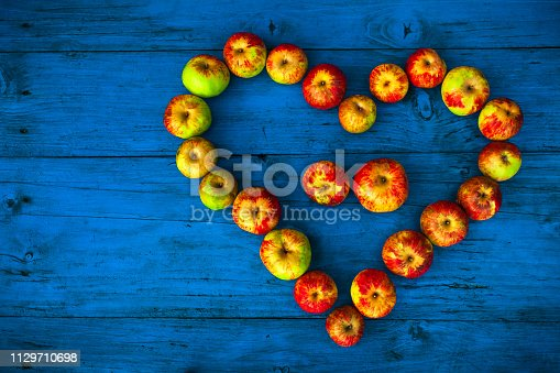 istock Heart Shape With Homegrown Organic Apples on Wooden Table 1129710698