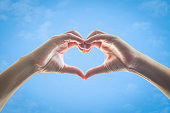 Heart shape woman hands against blue sky background