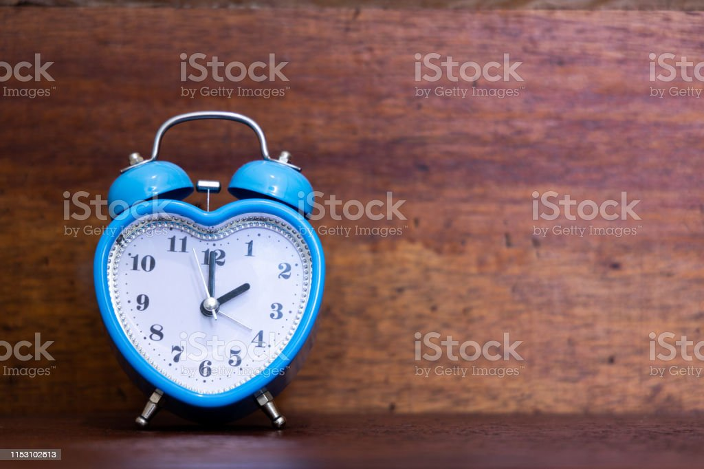 Heart shaped alarm clock on wooden background. Time is Two O Clock
