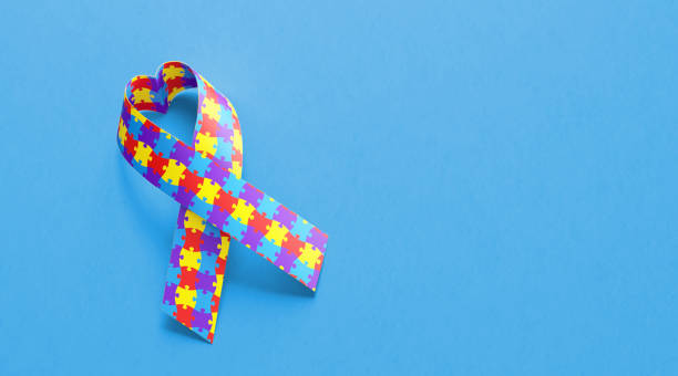 Heart Shaped Autism Awareness Ribbon On Blue Background stock photo