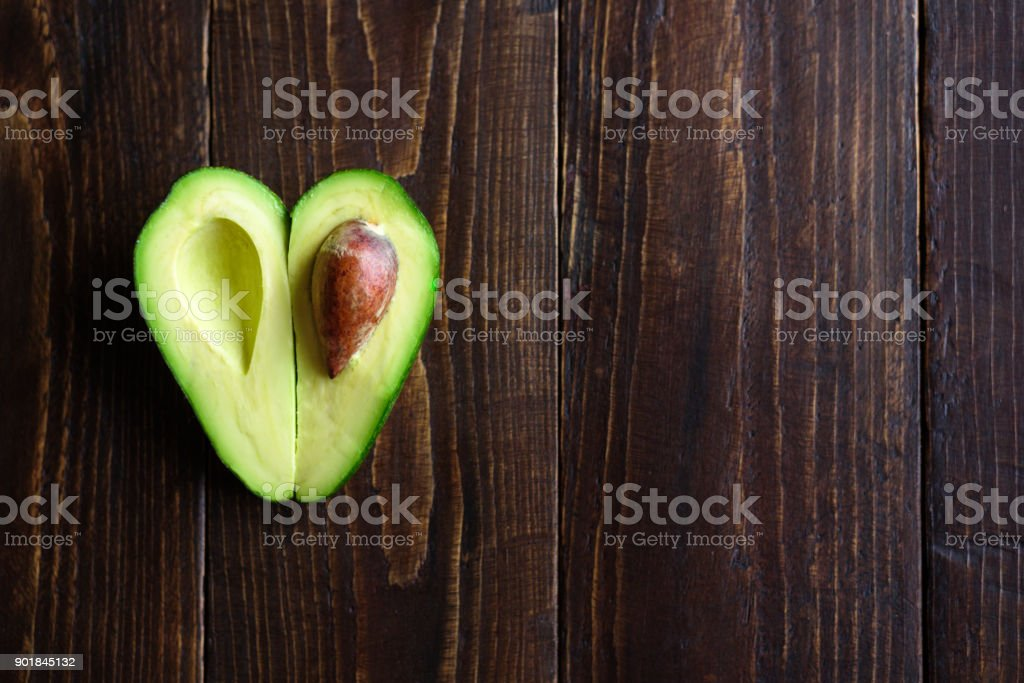 Heart shaped avocado on wooden background stock photo
