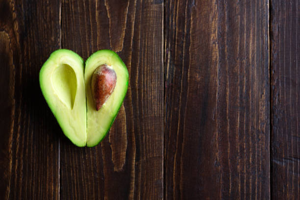 Heart shaped avocado on wooden background stock photo
