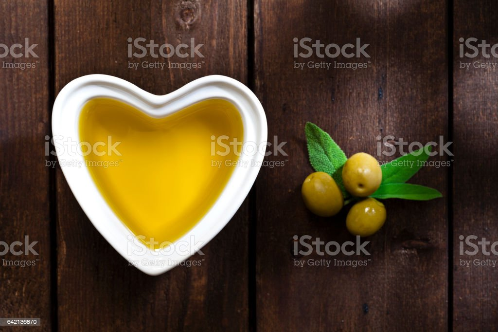 Heart shaped bowl filled with olive oil stock photo