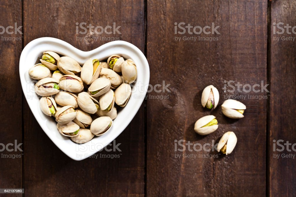 Heart shaped bowl filled with pistachios stock photo