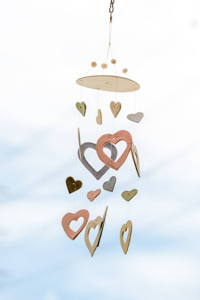 Heart Shaped Ceramic Wind Chimes Hanging On Window And Defocused Sky