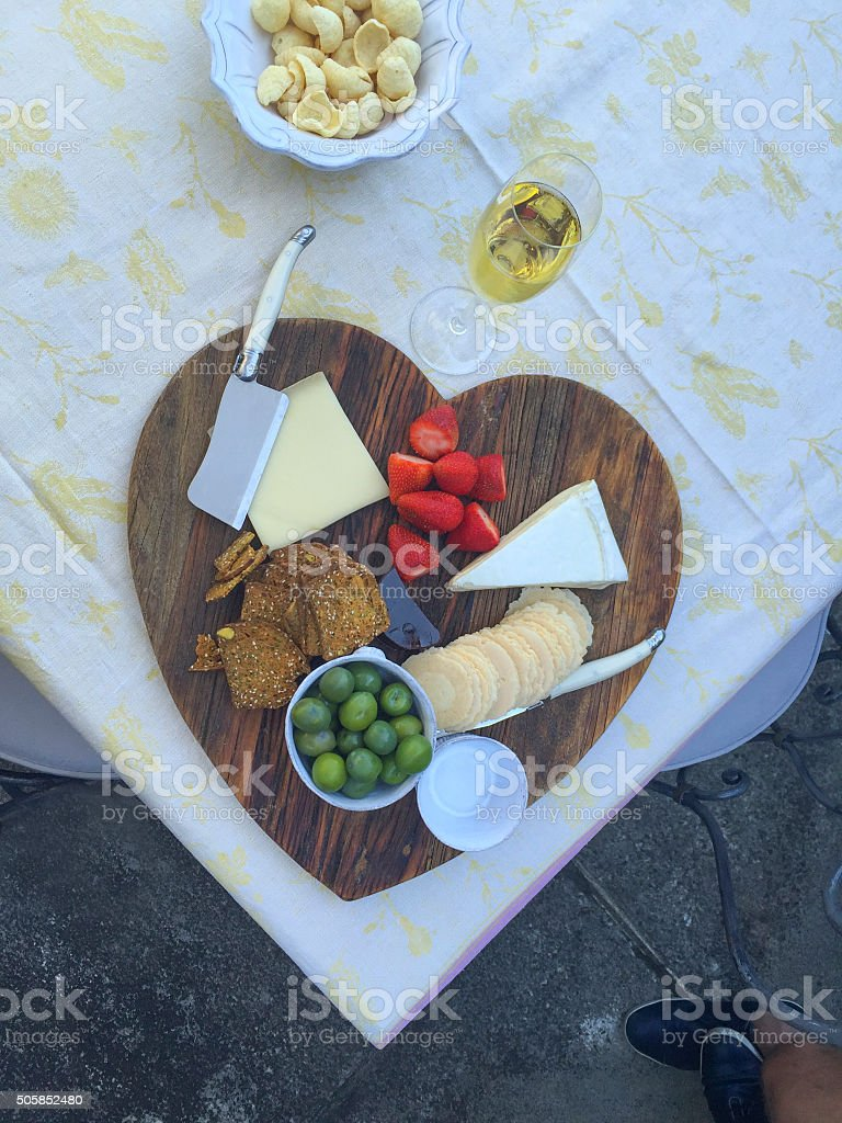 Heart shaped cheese board. Shot on iphone stock photo