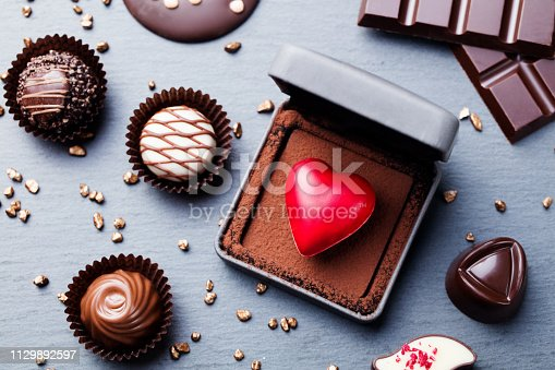 Heart shaped chocolate candy in a gift box on slate background. Top view