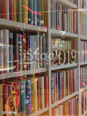 1057183432 istock photo Heart shaped christmas decoration on book shelves background, 2019 1071391182