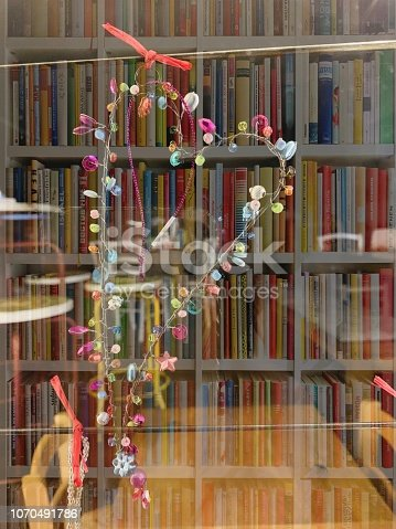 1057183432 istock photo Heart shaped christmas decoration on book shelves background 1070491786