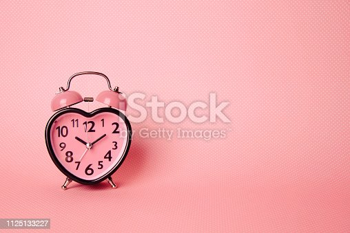 istock Heart shaped clock on pink background. Valentines day and love and duration concept. 1125133227