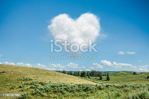 Heart Shaped Cloud in the Blue Sky with Rolling Landscape Background.