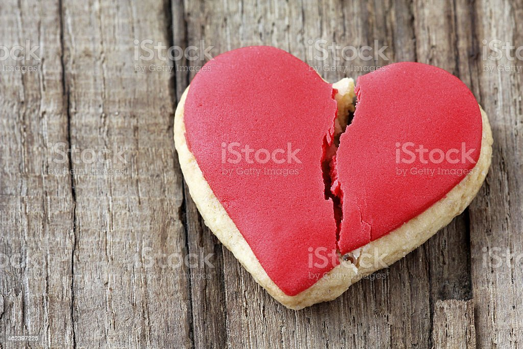 A heart shaped cookie cracked in the middle stock photo