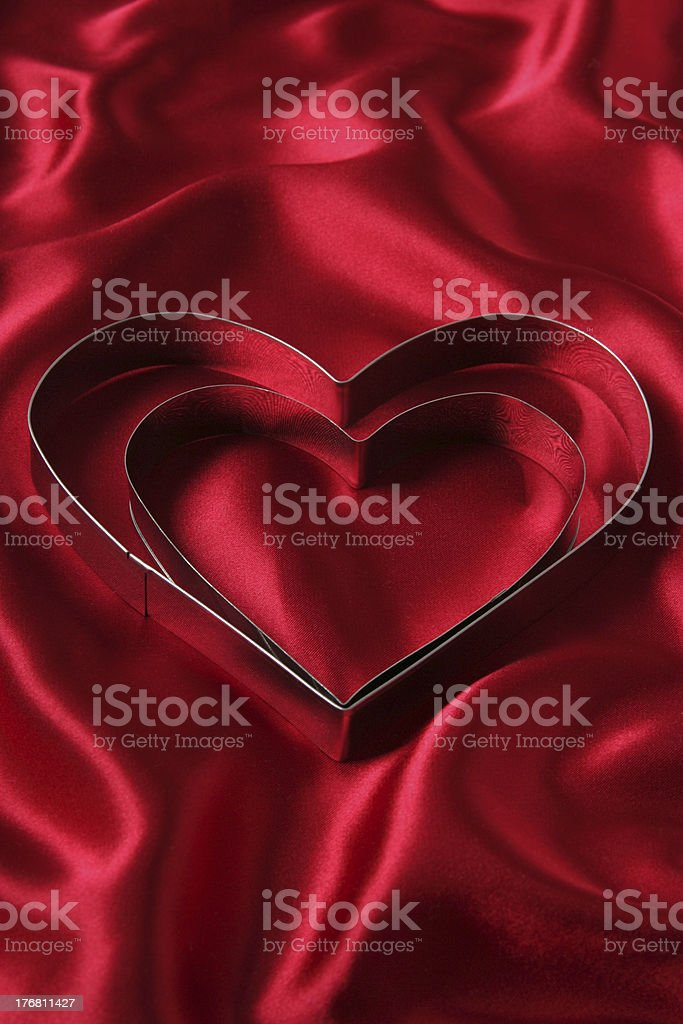 Heart Shaped Cookie Cutters on Red Satin royalty-free stock photo