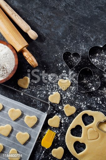 Making of heart shaped cookies with pastry dough and cookie cutter on kitchen counter