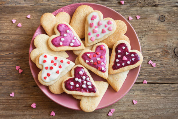 cookies in herzform zum valentinstag - hausgemachte zuckerplätzchen stock-fotos und bilder