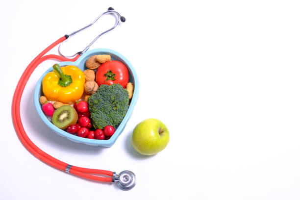 Heart shaped dish with vegetables and stethoscope stock photo