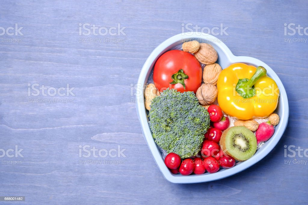 Heart shaped dish with vegetables isolated on blue wooden background stock photo