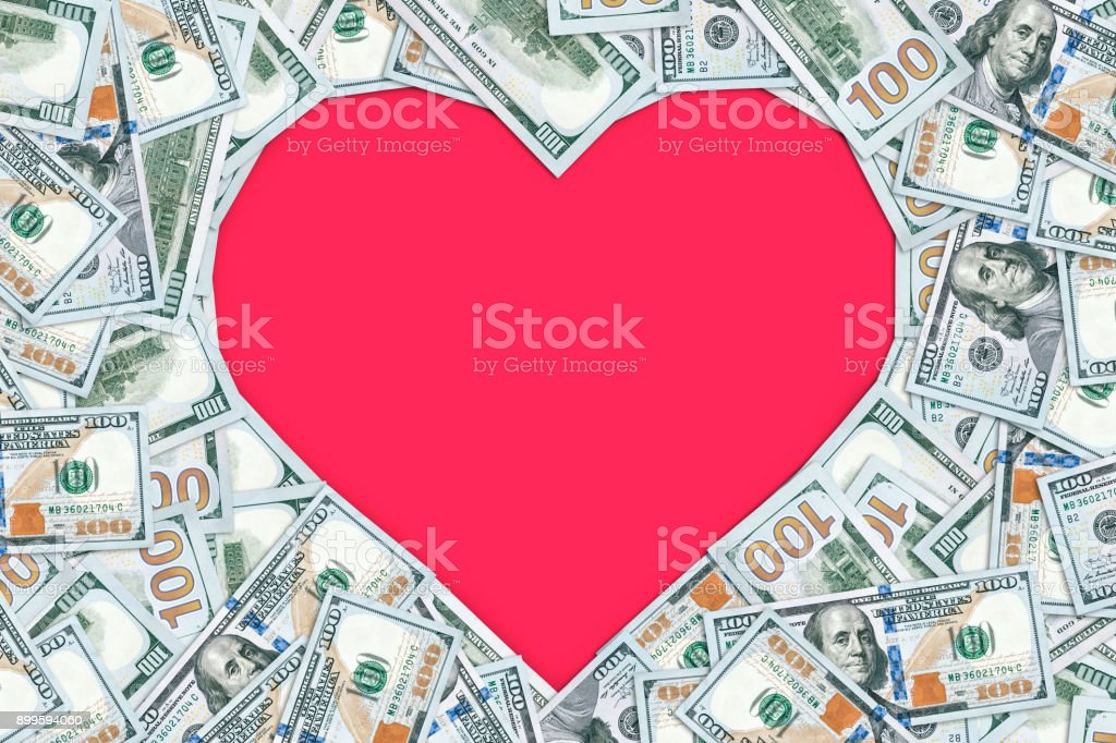 Heart shaped empty frame made with many 100 dollar banknotes stock photo