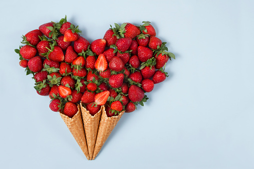 Freshly harvested strawberries designed in heart shape in ice cream cones over soft blue background