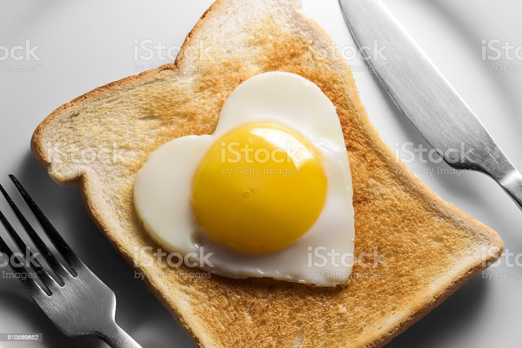 Heart shaped fried eggs on white toast and plate stock photo