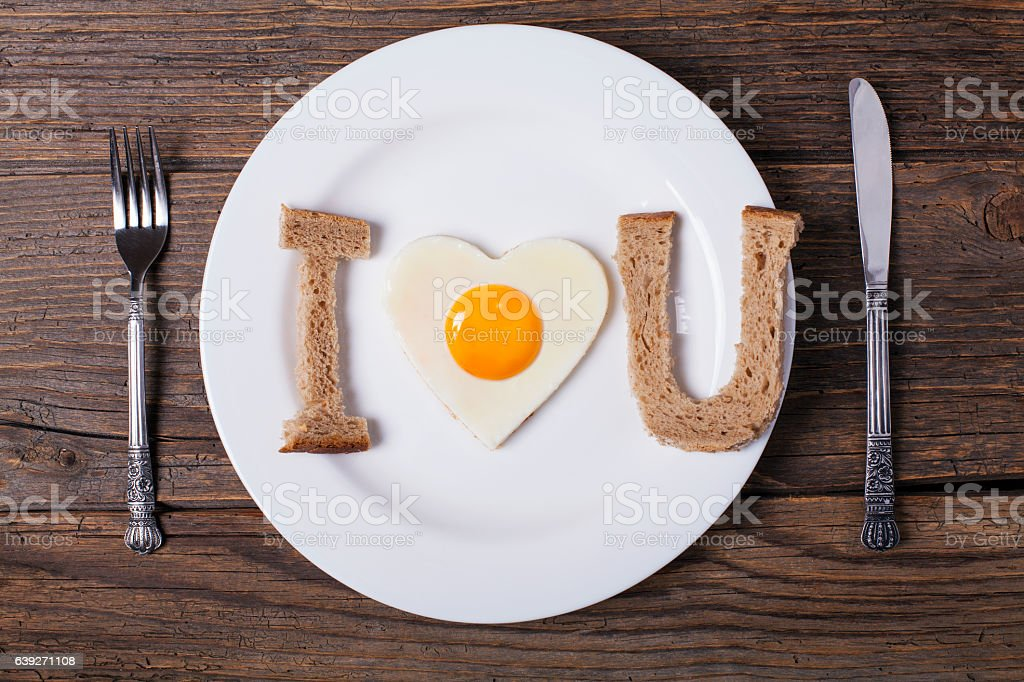 Heart shaped fried eggs with bread in plate stock photo