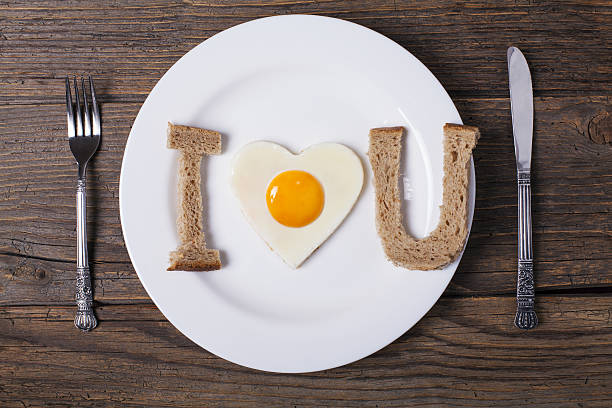 heart shaped fried eggs with bread in plate - i love you stock photos and pictures