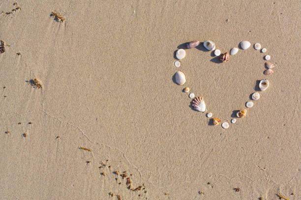 In Herzform aus Schalen liegt am Strand im Sand auf Koh Samui – Foto
