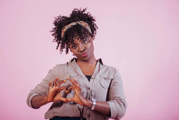 Herzförmige Geste. Attraktive afro-amerikanische Frau in lässiger Kleidung am rosa Hintergrund im Studio – Foto