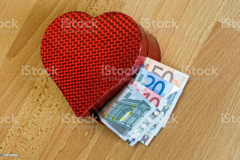 Heart shaped gift box full of cash stock photo