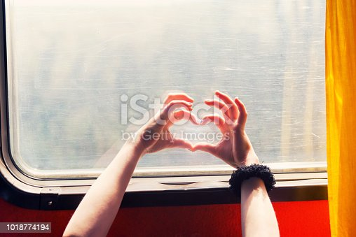 Heart shaped hands in front of the bus window