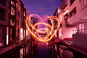 Huge red luminous heart hangs in the air over a small channel between two rows of apartments night photography, city lights night.