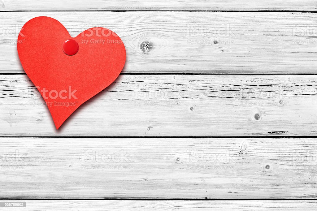 Heart shaped note on white weathered wooden wall stock photo