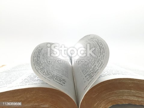 heart shape Bible book pages on white background close up
