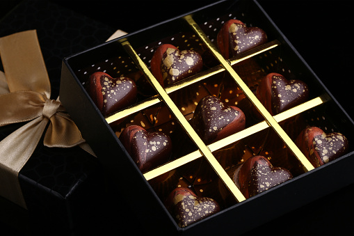Heart shaped painted luxury handmade bonbons in a gift box on a black background. Chocolates for Valentine's Day.