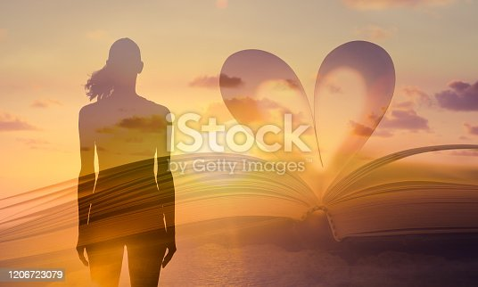 667312870 istock photo Heart shaped paper book against a beautiful sunset and silhouette of woman. 1206723079